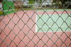 Wire fence with tennis court on background Stock Images