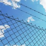 Wire fence with white clouds and blue sky background Stock Photos