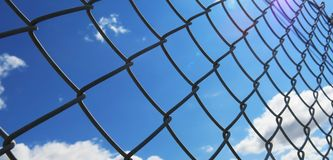 Wire fence with white clouds and blue sky background. Barbed wire fence with white clouds and blue sky background Stock Photos