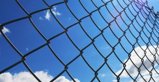 Wire fence with white clouds and blue sky background Royalty Free Stock Photos