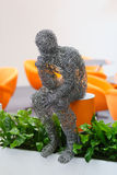 Wire figure of sitting man, grass and orange. Background stock photos