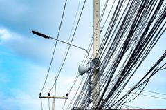 Wire, fluorescent lamp and loudspeaker on electric pole in Thailand with blue sky. stock image
