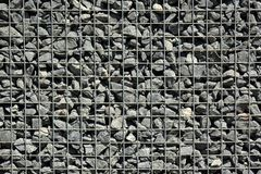 Wire Gabion Rock Fence. Metal Cage filled with rocks. Texture background of rock fence with cage. stock image