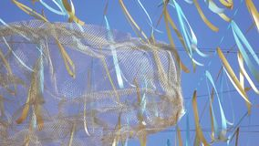 Decorative tape and cloud. On the wire hang yellow-blue decorative ribbons and a decorative cloud of transparent mesh stock video