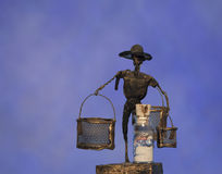 Wire image of man. Wire crafted figure with a hat displaying two baskets and a bottle beach sand Stock Image
