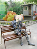 Wire man reading book. Contemporary art: the man made from colored wire and computer parts is sitting on the bench in park and is reading the book, Kiev stock photos