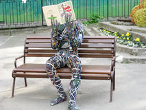 Wire man reading book. Contemporary art: the man made from colored wire and computer parts is sitting on the bench in park and is reading the book, Kiev Royalty Free Stock Images