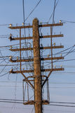 Wire mess on the old wooden rusty pylon. stock photos