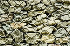 Wire net Gabion Rock Fence in close-up. royalty free stock photo