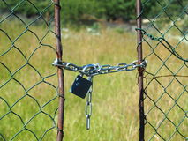Wire netted fence locked by metail chain and padlocked Royalty Free Stock Photography