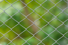 Wire netting fence. Close up old and dirty wire netting fence with green color blur background Royalty Free Stock Image