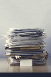 Wire Office Tray Piled Up with Papers. A wire office tray with blank label, piled up with papers and folders, undersaturated in drab hues for dreary, dystopian Royalty Free Stock Photos
