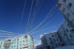 Wire plastered with snow. Against the clear blue sky between the roofs of houses, Yakutsk, Russia Stock Image