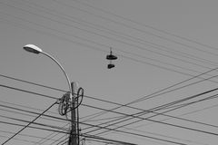 On the wire. Power lines with shoes hanging on them Stock Photography