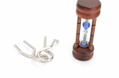 Wire puzzle and Hourglass. Wire puzzle (Puzzle ring)  and Hourglass on a white background Stock Images