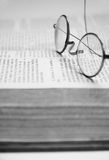 Wire Rimmed Glasses on a Book Royalty Free Stock Image