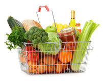 Wire shopping basket with groceries on white royalty free stock images