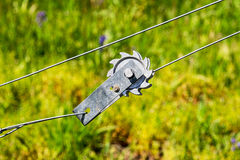 Wire Tension Hardware. A wire tension device used to increase the tautness of wire fences against a green background Royalty Free Stock Image