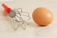 Wire whisk and brown egg Royalty Free Stock Images