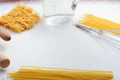 Wire whisk, macaroni and rolling pin on flour Royalty Free Stock Photography