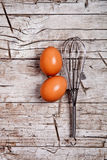Wire whisk and two brown eggs Stock Photos