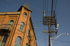 Wired. Colonial building connected by wires to an electricity post Stock Image