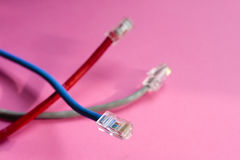 Wired communications. Ethernet cables overlapping against a pink background Royalty Free Stock Photography