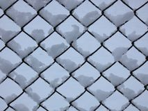Wired Fence after Blizzard � Pattern. Chain link fence in winter covered by snow Royalty Free Stock Photo