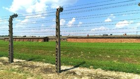 Wired fences of concentration camp. Prison barracks in background stock video