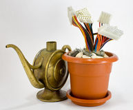 Wired flower pot with old oil can. Wired flower pot with connectors and electronic circuits near an old oil can Royalty Free Stock Photo