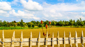Wired picket fence around a freshly plowed farmers field Stock Photo