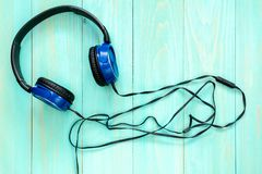 Wired stereo headphones. On blue wooden background stock photography