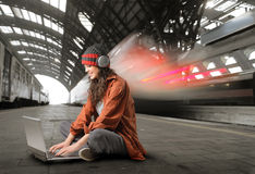 Wireless. Young woman sitting on the platform of a train station and using a laptop Royalty Free Stock Photography