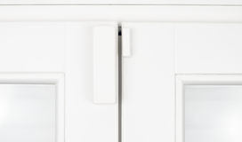 Wireless alarm sensor window door on white sash Royalty Free Stock Photos