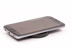 Wireless black mobile charger with mobile phone isolated over white background Royalty Free Stock Images