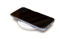 Wireless charging. Smartphone on charging pad Stock Images