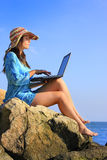 Wireless communication. Beautiful woman with her laptop on the rocks Stock Photos