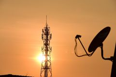 Wireless Communication Antenna With sunrise. Bright sky.Telecommunication tower with antennas with orange sky Royalty Free Stock Photos