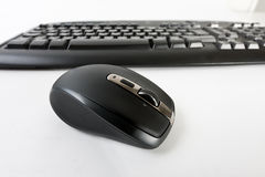 Wireless computer mouse. Close-up of a wireless computer mouse with a wireless computer keyboard in the background Stock Images