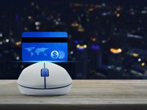 Wireless computer mouse with blue credit card on wooden table over blur light city tower, Online e-payment concept royalty free stock photography