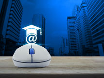 Wireless computer mouse with e-learning icon on wooden table in Royalty Free Stock Photography