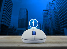Wireless computer mouse with information sign icon on wooden tab Stock Photos