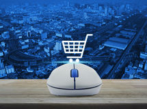 Wireless computer mouse with on line shopping icon on wooden tab Royalty Free Stock Photo