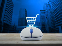 Wireless computer mouse with online shopping icon on wooden tabl Stock Photo
