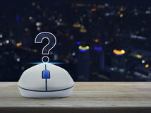 Wireless computer mouse with question mark sign icon on table Stock Image