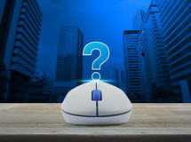 Wireless computer mouse with question mark sign icon on wooden t Royalty Free Stock Image