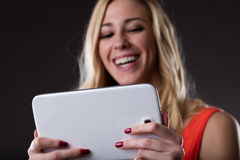 Wireless connected digital tablet held by a smiling blonde woman Royalty Free Stock Images