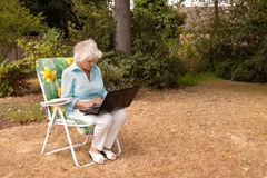 Wireless Connection. An elderly woman using a laptop computer in her garden Royalty Free Stock Image