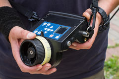 Wireless follow focus. Male hands hold the wireless follow focus system during the filming process Stock Photo