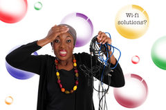 Wireless. Frustrated african woman standing with wires in her hand.  Wireless solutions in the background Stock Photography